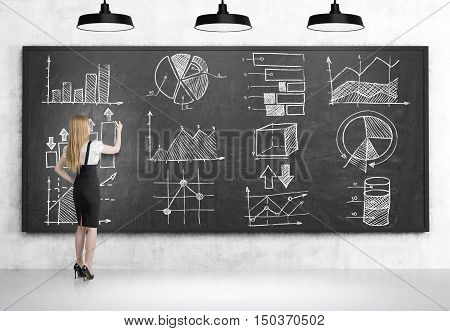 Side view of blond girl drawing graphs on blackboard in room with concrete walls and floor. Concept of statistics in business management
