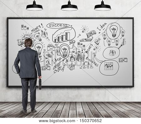 Rear view of businessman with suitcase looking at giant business sketch on whiteboard in room with wooden floor. Concept of bull's eye