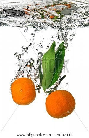 tangerine dropped into water with bubbles on white