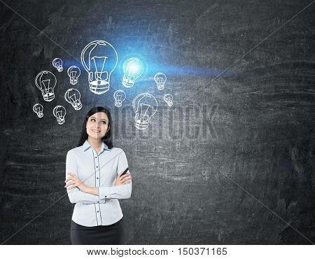 Dreamy girl with black hair standing near blackboard with blue light bulbs on it. Concept of ideas. Mock up