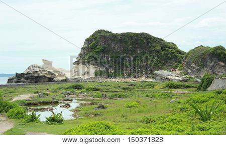 Kapurpurawan Rock Formation in Ilocos. Breathtaking view of grass, field, mountain, pond and ocean.