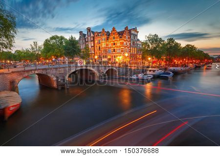 Amsterdam canal, bridge and typical houses, boats and luminous track from the boat during morning twilight blue hour, Holland, Netherlands.