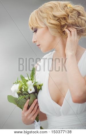 Portrait of a young beautiful bride looking down gently embraces wedding bouquet and touching her hair outdoors on gray background. Professional make-up and hair-style. Side view.