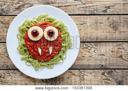 Green spaghetti pasta creative halloween food vampire monster with fake blood tomato sauce and big mozzarella eyeballs holiday decoration kid party meal on vintage wooden table background.
