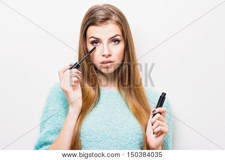 Beautiful young blonde Caucasian modern woman applying mascara. Gorgeous young teenage girl with long hair applying mascara using brush, wearing light green sweater. Retouched, no filter, studio light