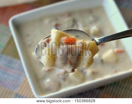 Spoonful of Clam Chowder Soup. Close up - viewed above  bowl.
