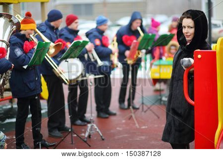 Brass band of six musicians play on playground and women poses at winter day, focus on woman