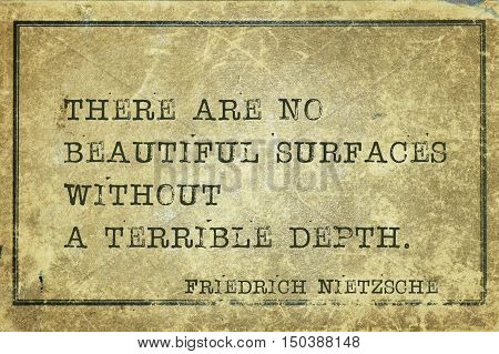There are no beautiful surfaces without a terrible depth - ancient German philosopher Friedrich Nietzsche quote printed on grunge vintage cardboard