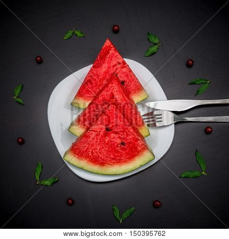 Slices of fresh jucie red watermelon on the white plate served with fork and knife. Decorated with mint and wineberry on black background.