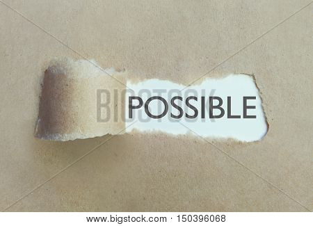 Torn brown paper uncovering the word possible