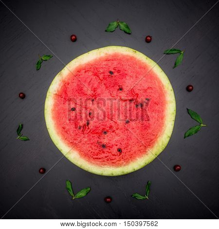 A half of fresh jucie red watermelon on black background. Decorated with mint and wineberry.