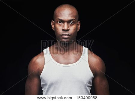 Single serious young black man with shaved head and unemotional expression in white undershirt over dark background