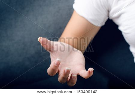 Woman show a gesture with hand. Woman´s hand. Spasm hand. Dark blue background.
