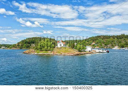 White small finnish wooden sauna log cabin on island at summer