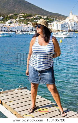 Portrait of adult beautiful woman in straw hat wearing striped top and denim skirt walking on gangway over the sea