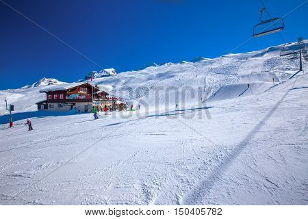 HOCH-YBRIG, SWITZERLAND, February 2015: Skiers skiing on ski slopes near Alperestaurant Staefel on the top of Hoch Ybrig resort Switzerland