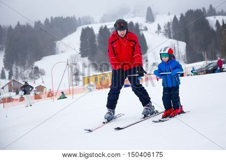Happy little boy learning skiing with his father during winter holidays in Swiss Alps