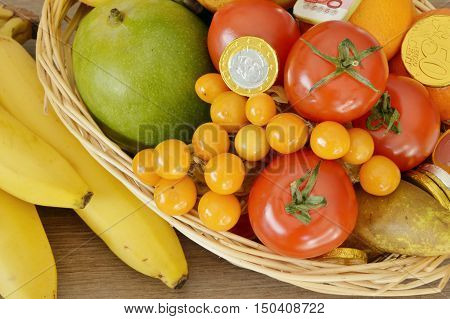 fruits are the treasures of nature. fruits and chocolate coins in the basket