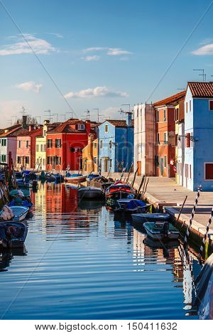 Burano island in Venice. Italy. Motley coloured home coast with boats floating on Channel. Blue sky and evening sunset