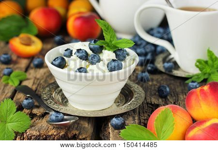 Cottage cheese with blueberries diet breakfast morning meal. Fresh summer fruit apricots and berries on wooden table in rustic style. Beautiful composition and concept of healthy food selective focus