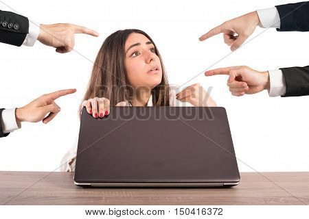 People pointing a woman hidden behind a computer