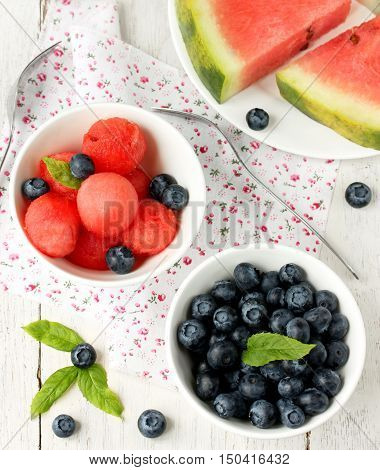 The beads of juicy watermelon and berries fresh blueberries on a white table