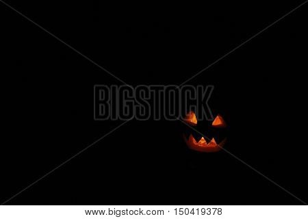 bared teeth of Halloween pumpkin ghost with burning within. Ghost of Halloween with black empty place for text