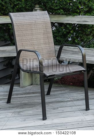 Outdoor woven chair with only three legs touching an outdoor wooden deck.