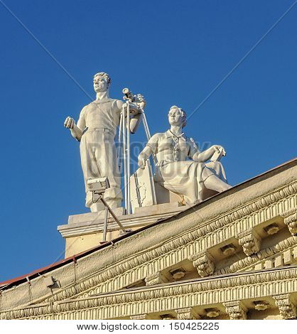 Minsk, Belarus - September 13, 2016: Sculpture of man with theodolite and sitting women on the roof of Trade Union Palace in Minsk. Stalin's era style.