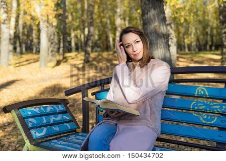 Girl sits on a park bench and reading a book sunny autumn day in October. Yellow leaves underfoot and the trees.