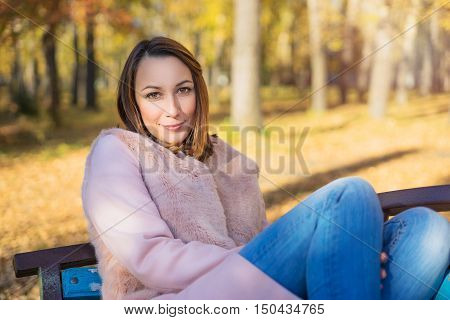 Girl sits on a park bench sunny autumn day in October. Yellow leaves underfoot and the trees.
