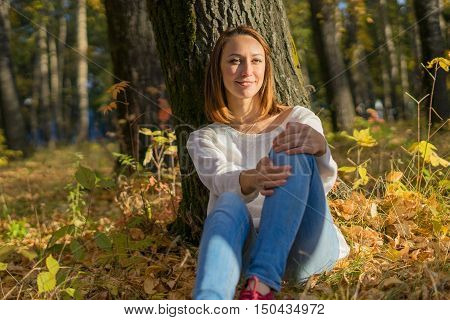 Young girl sitting under a tree in the forest sunny autumn day. Autumn nature relaxation and enjoyment the smile on her face