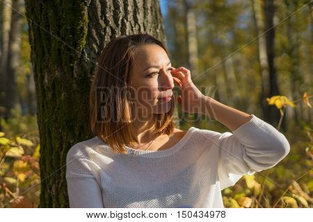Young girl sitting under a tree in the forest sunny autumn day. Autumn nature relaxation and enjoyment