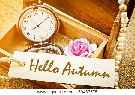 Hello Autumn on paper tag with vintage pocket watch and rose in wooden box on wooden background.