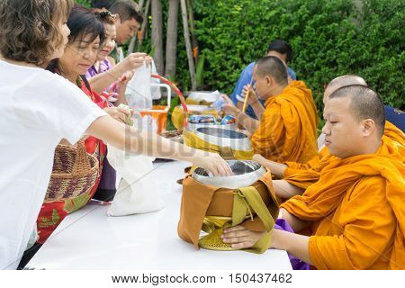BANGKOK, THAILAND ,27 August 2016 : people put food offerings in a Buddhist monk's bowl.
