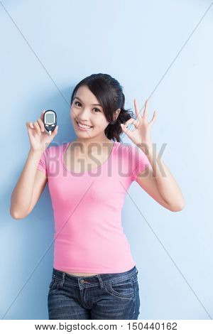 Woman holding a blood glucose meter to prevention diabetes isolated on blue background asian