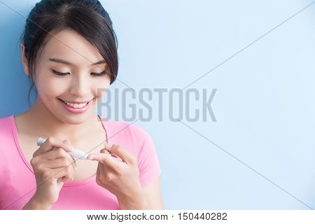 Woman collecting blood to prevention diabetes isolated on blue background asian