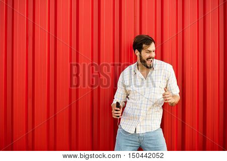 Adult Man With Cellphone Dancing On Red Background