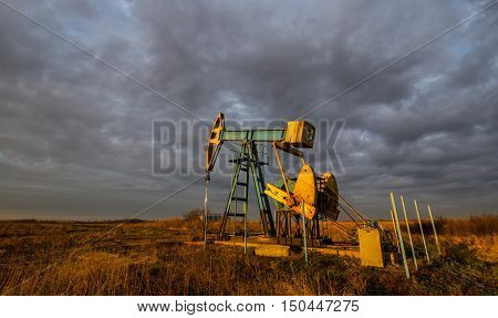 Oil derricks on a background of beautiful sunset and storm cloudscape