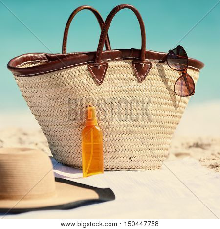 Women's beach accessories for summer vacation. What to bring for holiday concept. Straw tote bag, sun hat and sunscreen lotion or suntan tanning oil spray bottle for travel holidays.