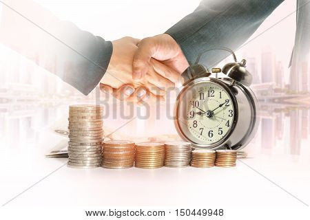 Double exposure of hand shaking of business people with a row of stack money coins and analog clock on the blurred cityscape background concept for business finances and saving money.