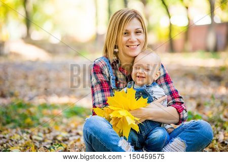 Happy young mother playing with baby in autumn park with yellow maple leaves. Family walking outdoors in autumn. Little boy with her mother playing in the park in autumn.
