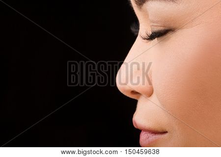 Closeup of woman posing with her eyes closed over black background in studio.