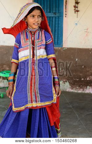 BHUJ INDIA - JANUARY 13: The young girl in the ethnic dress from the Gujarat state is going for water to the desert Bhuj in January 13 2015