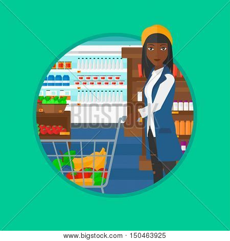 An african-american young woman pushing a supermarket cart with some goods in it. Customer shopping at supermarket with cart. Vector flat design illustration in the circle isolated on background.