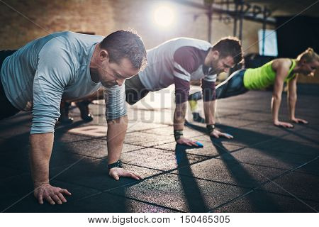 Group of adults performing push up exercise drills at indoor physical fitness cross-training exercise facility with bright light flare over them