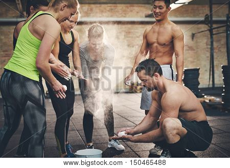 Athletic adults applying talcum powder to hands before doing intense workouts requiring a firm grip