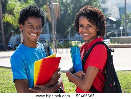 Two happy african american students outdoor on campus of university