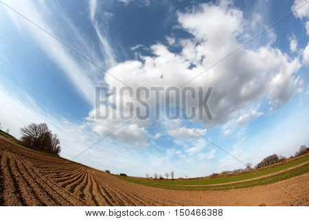photographed fisheye landscape with a plowed field sky and clouds