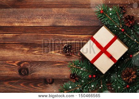 Christmas background of gift box, fir tree and conifer cone on rustic wooden table top view. Snow effect. Flat lay.